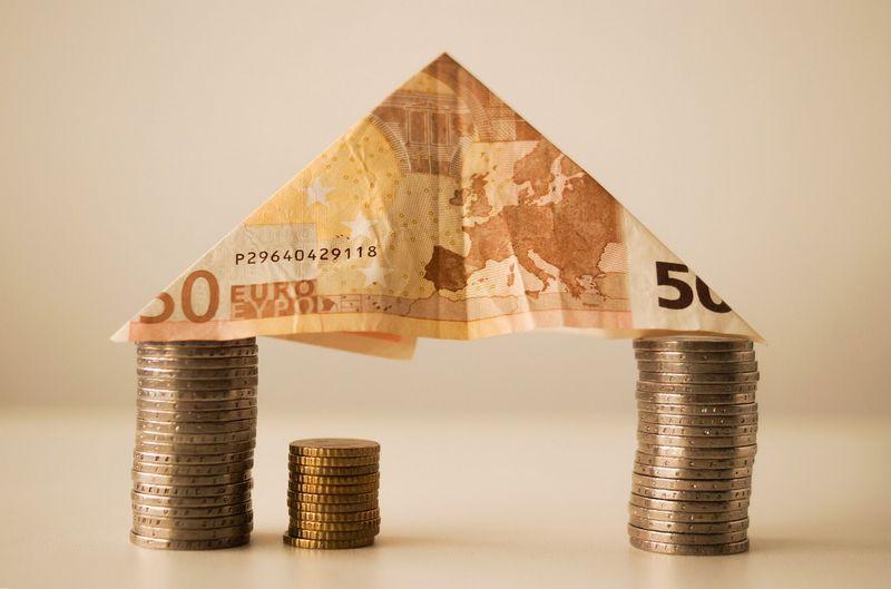 Gastos Hipotecarios - Casa formada con monedas apiladas y un billete de 50 euros